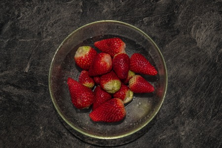 Making of young strawberries with sugar on black table in white tile kitchen