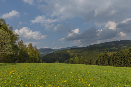 Green meadows in spring sunny cloudy day near Branna town in Jeseniky moravian mountains