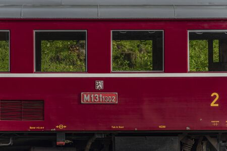 Red old historical diesel train with cargo green car in Ceska Kamenice town in spring day Banco de Imagens