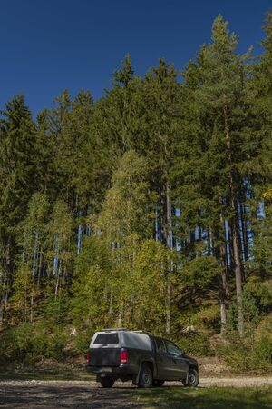 Big blue off-road car with white roof in color autumn forest in national park and mountains Sumava