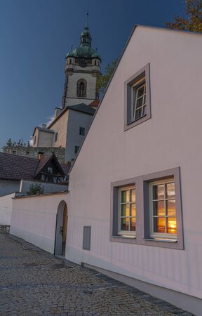 Old house with sunset in window in autumn evening in Melnik town