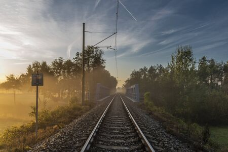 Electric railway track in color morning with fog and autumn color fresh air