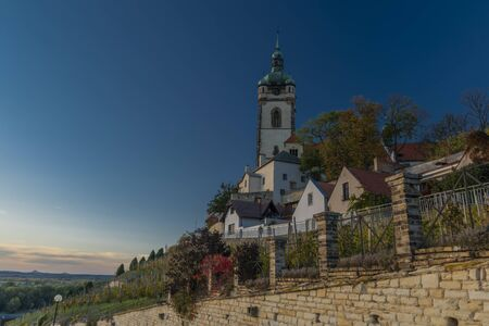 Church castle and old houses in old town Melnik in central Bohemia in autumn color evening