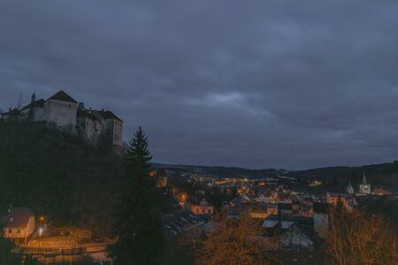 View over Vimperk town in winter dark cold evening in centre of national park Sumava with castle