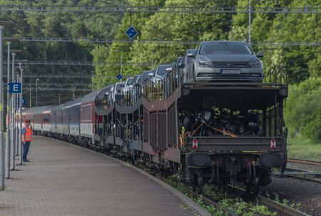 Night train with sleeping coaches and car and motorcycle coaches in Kysak station in summer hot morning