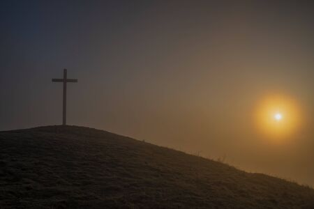 Sunrise on Radobyl hill with big cross and small statue in winter cold morning Фото со стока