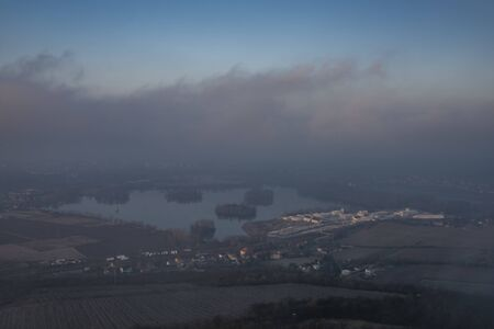 Sunrise time on Radobyl hill over valley of river Labe and Litomerice town in winter morning