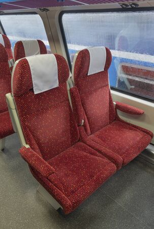Double decker electric multiple unit interior with red seat in first class coach