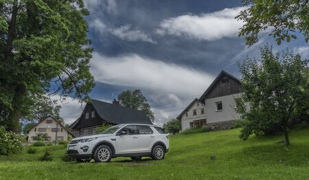White big offroad car in counry village on green meadow in blue sky clouds day