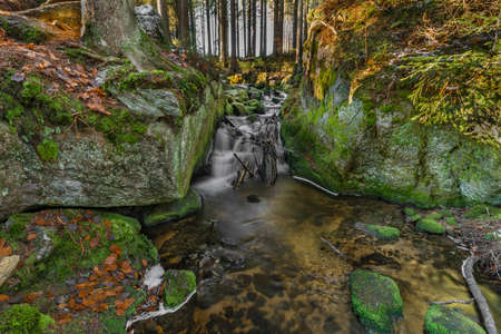 Konsky creek in National park Sumava with cascade and waterfall in winter sunny cold day