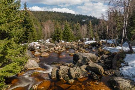 Color Jizerka river near confluence with Jizera creek in spring winter sunny cold windy day Reklamní fotografie