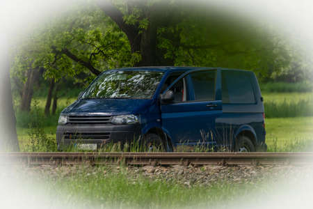 Blue big van on path in green spring fresh nature