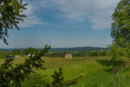 Meadows and forests near Javornik hill and village in Sumava national park in spring evening