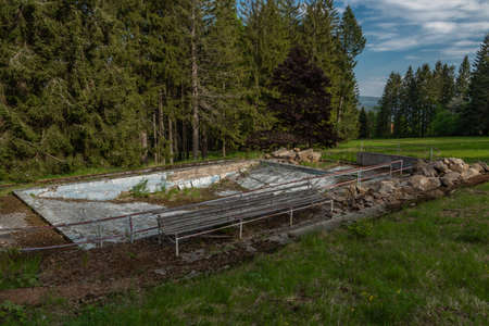 Old swimming pool near Javornik hill and village in Sumava national park in spring evening