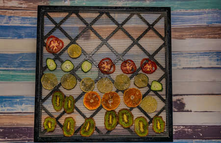 Dry color fruit and vegetable on color wooden table and black drying net