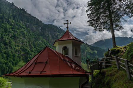 Wolfaukapelle chapel in sunny cloudy morning in Austria color mountains