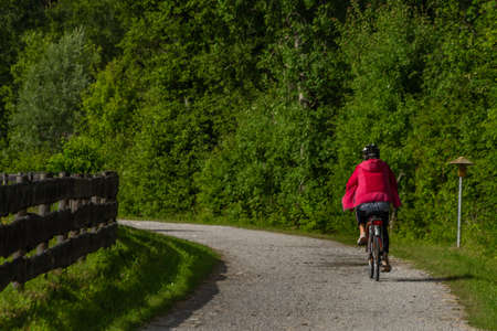 Path with red dressed woman on bicycle near wooden fence and color fresh meadow Reklamní fotografie