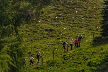 Tourists on big slope in Austria summer mountains