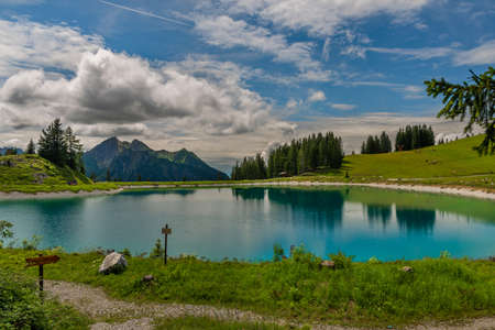 Nice blue green lake on big mountains in Austria summer cloudy fresh day
