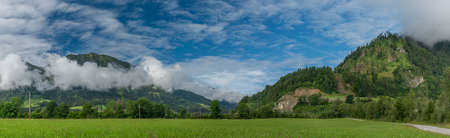 Hills and valley near Sankt Johann im Pongau with fog and green fresh meadows 写真素材