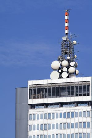 the antennae: Cluster of different microwave antennae on top of a high rise modern office building Stock Photo