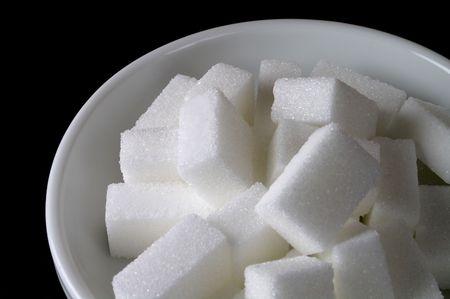 sucrose: White ceramic sugar bowl with sugar cubes in black background (closeup)