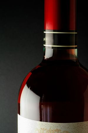 aperitive: Red wine bottle closeup with red capsule (closeup)