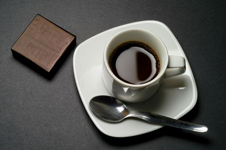 coffee hour: Coffee cup with wrapped chocolate, biscuit, etc.  on dark grey background closeup