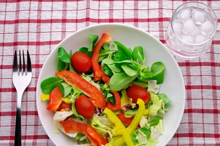 Salad with water glass on tablecloth - high angle view closeup Stock Photo - 962642