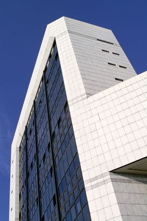 Modern sleek office building with white marble tiles in a blue sky Stock Photo - 963556