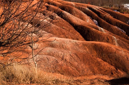 badland: A badlands  also badland  is a type of dry terrain where softer sedimentary rocks and clay-rich soils have been extensively eroded by wind and water  Stock Photo