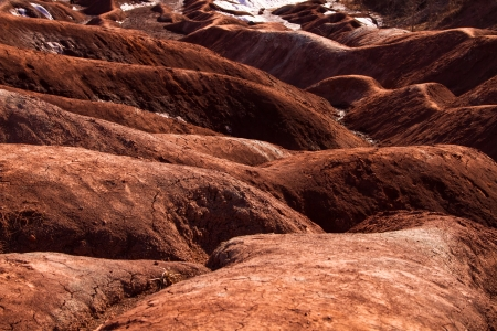 badland: A badlands  also badland  is a type of dry terrain where softer sedimentary rocks and clay-rich soils have been extensively eroded by wind and water