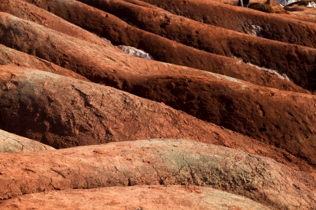 extensively: A badlands  also badland  is a type of dry terrain where softer sedimentary rocks and clay-rich soils have been extensively eroded by wind and water  Stock Photo