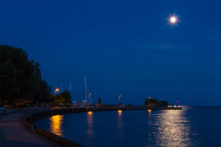 An evening by the harbor under a full moon with light reflections on the water photo