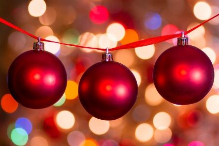 effets lumiere: Red Christmas balls suspendus � un ruban rouge avec des effets de lumi�re de f�te dans l'arri�re-plan