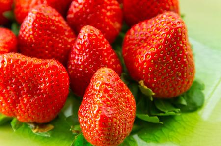 Fresh organic strawberries on green background