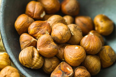 Hazelnuts on black bowl Stockfoto