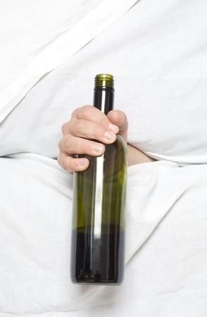 bedsheets: Bottiglia di vino in una mano tra le lenzuola. Bere problema nascosto. Archivio Fotografico