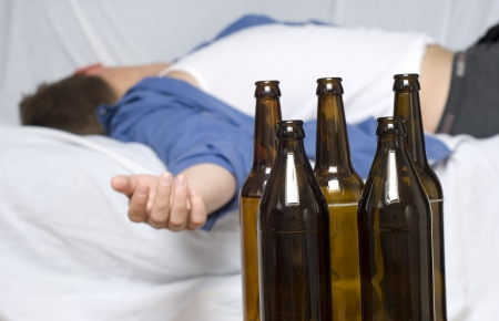 Businessman passed out on the couch. Empty beer bottles. photo
