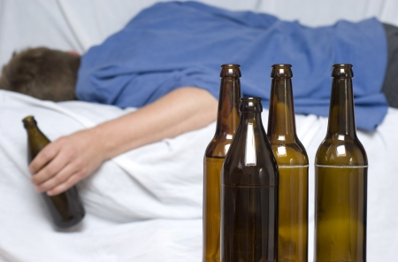 addiction alone: Man passed out with a beer bottle in his hand. Alcohol abuse Stock Photo