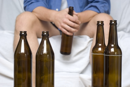 Man with beer bottles. Alcohol abuse and loneliness.