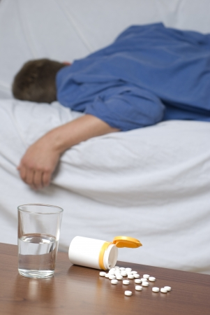 sleeping tablets: Glass of water and sleeping pills on the table.