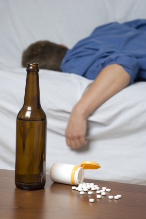 drug use: Businessman passed out on the bed after long day of work. Mixed alcohol and drug abuse.