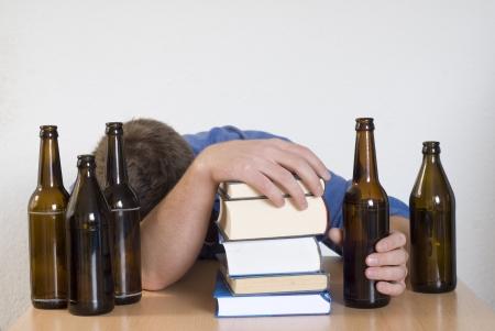 alcoholismo: Joven estudiante agotado durmiendo detrás de los libros y botellas de cerveza.