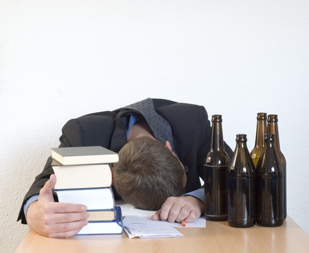 Passed out: Businessman sleeping at the desk after too many beers.
