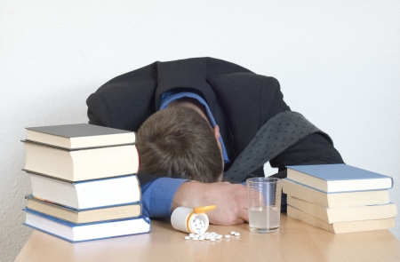 passed out: Businessman passed out in the office. Sleeping pills at the desk. Stock Photo