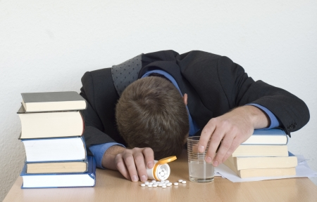 sleeping tablets: Businessman exhausted. Sleeping at the desk. Sleeping pills and glass of water.