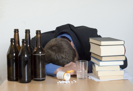 drug use: Businessman sleeping at his desk, surrounded by books, drugs and alcohol. Stock Photo