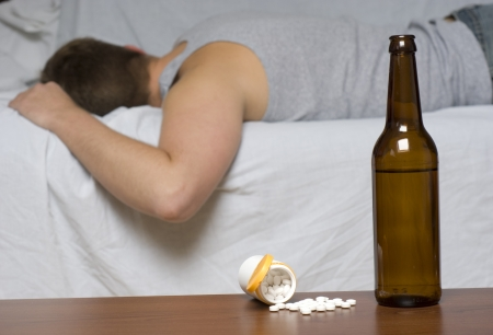 drunk man: Beer bottle and pills on the table. Man sleeping on the sofa.