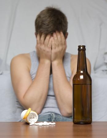 droga: Birra bottiglia e farmaci sul tavolo. Uomo depresso e solitario.